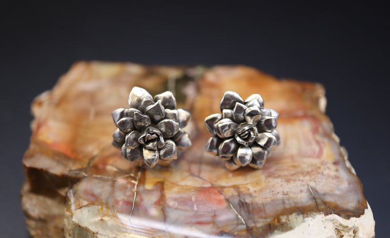 A pair of handmade sterling silver earrings made by The Striped Cat Metalworks are about 1 inch tall and shown on top of a light and dark brown piece of petrified wood.