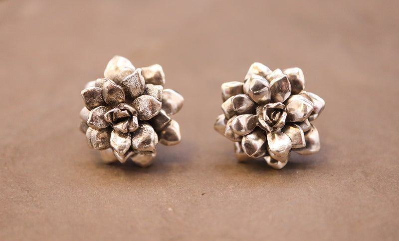 Small silver succulent earring studs are shown on top of a dark grey piece of slate.