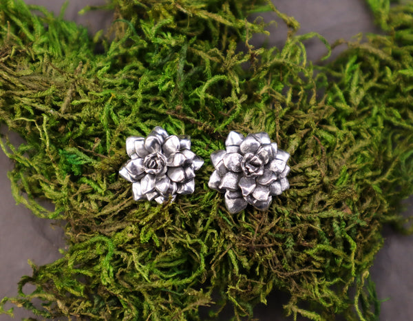 handmade sterling silver succulent post earrings made by The Striped Cat Metalworks in Massachusetts. They are about 1/2 inch tall and shown on top of some dried moss.