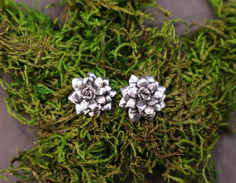 A pair of sterling silver succulent plant earrings are shown on top of a piece of dark green real moss.