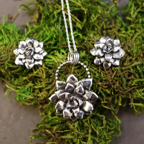A set of silver handmade necklace and earrings of succulent plants. They are shown together on a piece of dark green real moss and a grey slate stone.