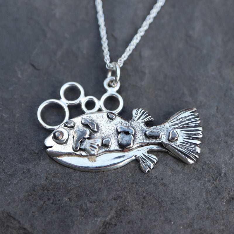 A handmade sterling silver dwarf pea puffer charm necklace is shown on top of a dark slate stone.