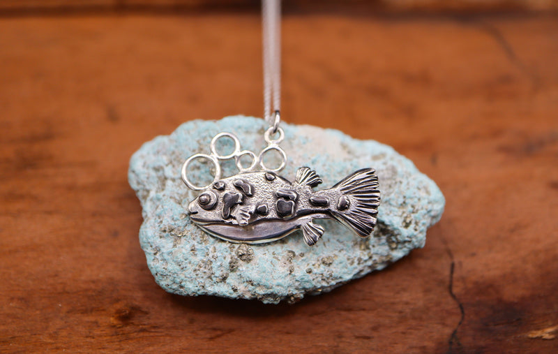 a 1 inch long sterling silver dwarf puffer fish is shown on top of a light blue turquoise stone.