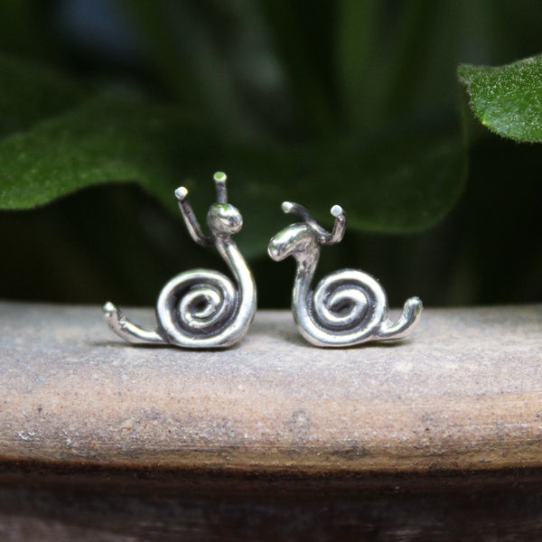 Handmade sterling silver small snail stud earrings are show on a piece of stone in front of some greenery.