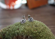 Load image into Gallery viewer, Small handmade silver snail stud earrings are shown on top of a green mound of real moss. Made by The Striped Cat Metalworks in Massachusetts.