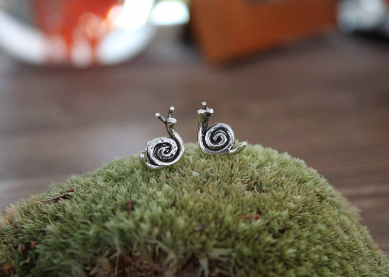 Small handmade silver snail stud earrings are shown on top of a green mound of real moss. Made by The Striped Cat Metalworks in Massachusetts.