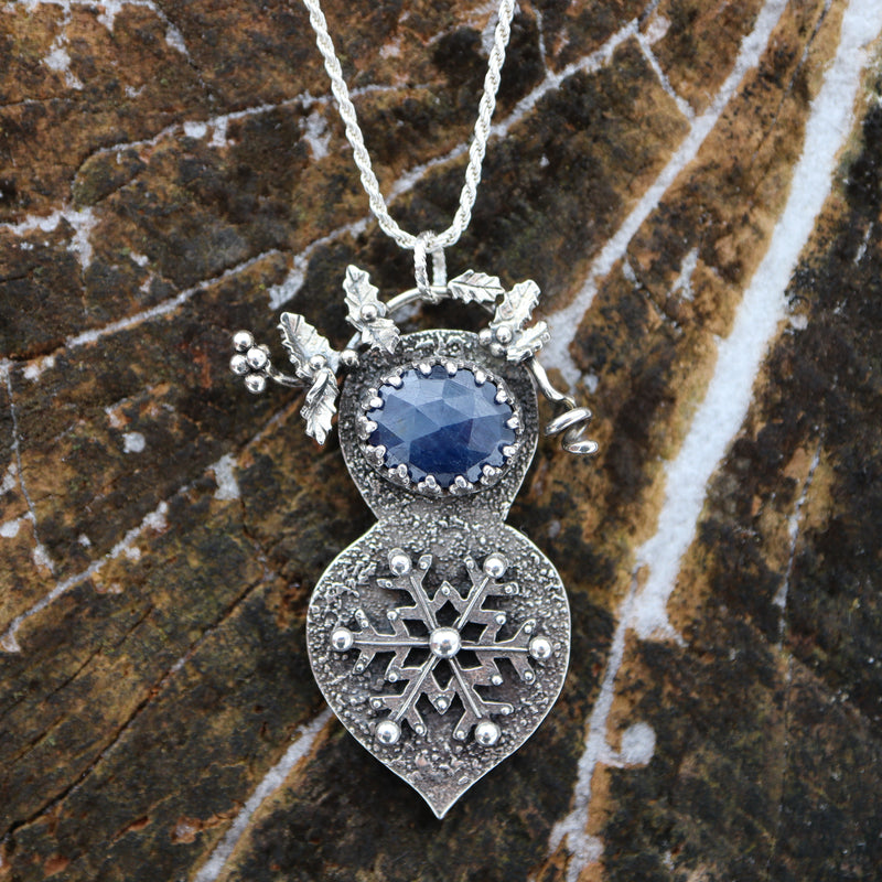 A sterling silver handmade snowflake necklace featuring a deep blue rose cut sapphire stone and a twig of tiny holly berries and leaves at the top. It is shown on a piece of dark brown wood.