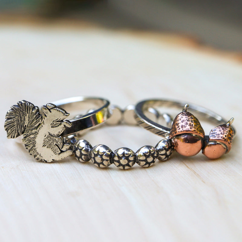 A set of three stacking rings featuring a hand carved squirrel, two copper acorns, and a floral band shown in a piece of light colored wood.