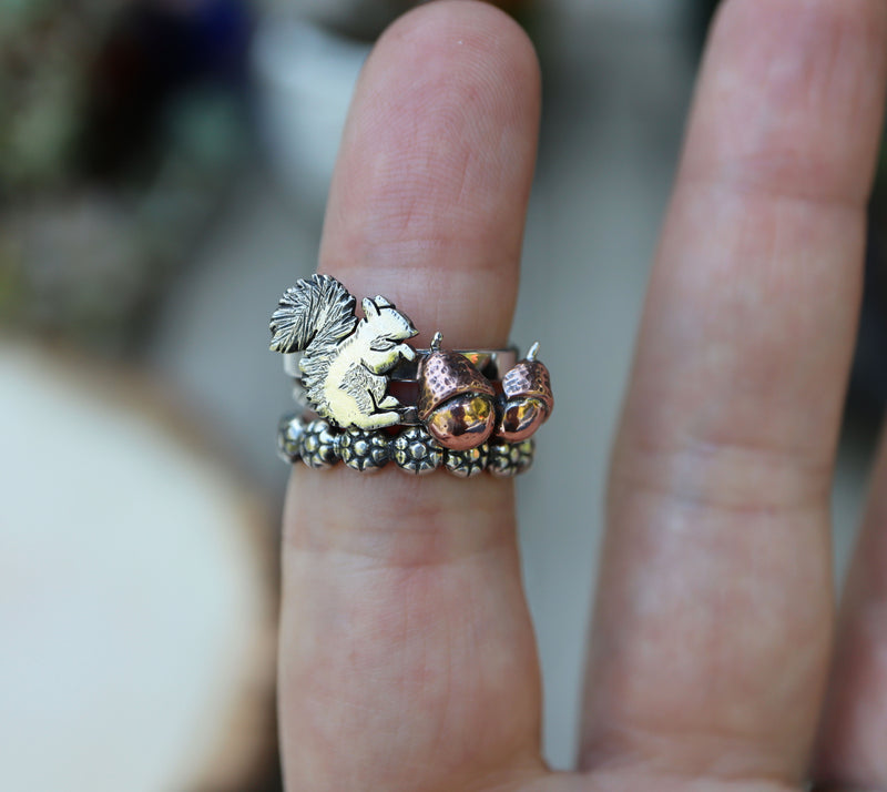 A set of three stacking rings with a squirrel, acorns, and flowers are shown being worn on a finger for size reference.