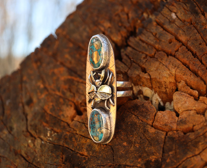 A side view of the silver and gold stag beetle ring. It shows the double ring band and the leaf patterned bezels holding the morenci turquoise stones.