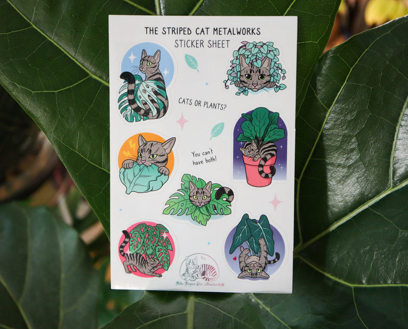 The Striped Cat Metalworks sticker sheet featring MAx the striped cat and houseplants like a fiddle leaf fig, monstera adansonii, monstera albo, string of hearts, and an alocasia polly all being played with by Max the cat! The stickers are shown on a real fiddle leaf fig plant.