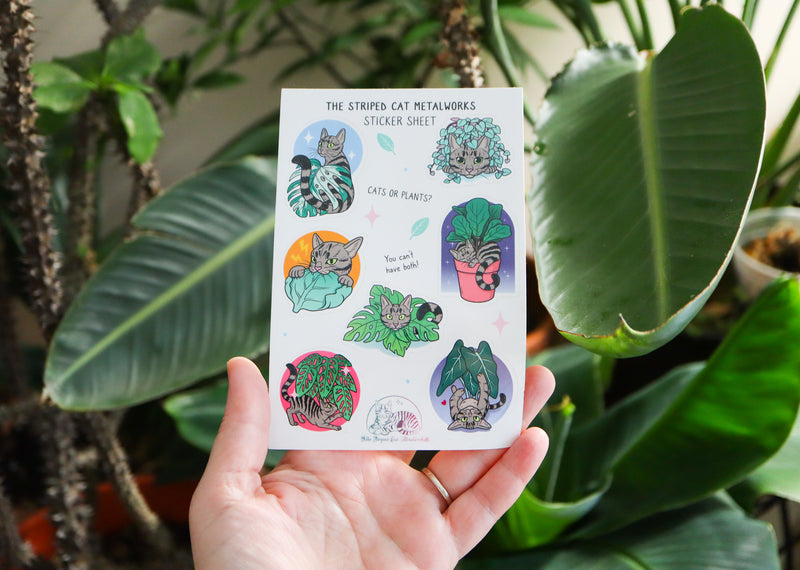 The Striped Cat Metalworks sticker sheet featring MAx the striped cat and houseplants like a fiddle leaf fig, monstera adansonii, monstera albo, string of hearts, and an alocasia polly all being played with by Max the cat! A hand is holding the sticker sheet in front of houseplants to show the size.