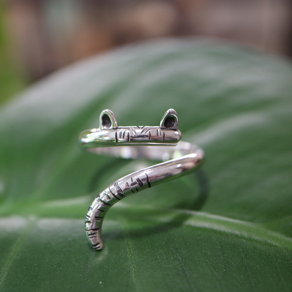 A handmade sterling silver cat ring that is made to wrap around your finger just like a cat's tail does. The ring has carved stripes at the end of the tail and on the forehead with two little ears soldered on top.