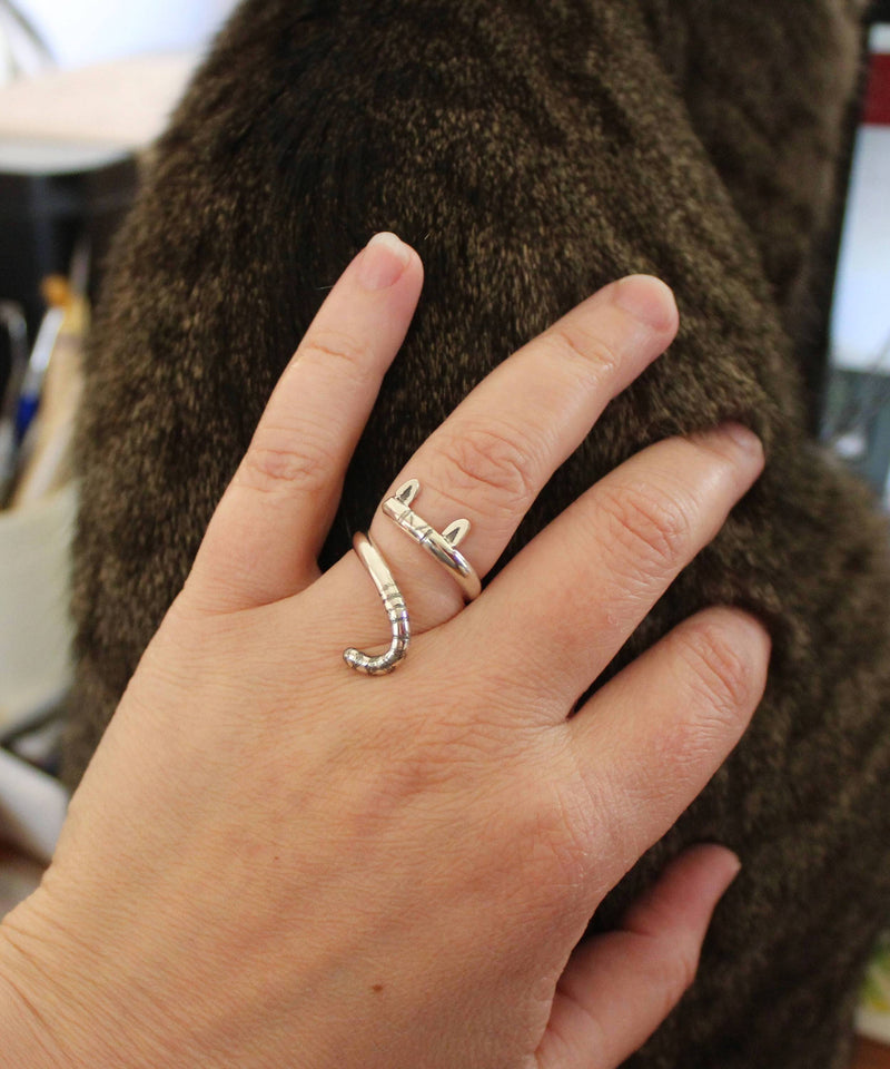 A hand wearing the adjustable sterling silver cat wrap ring while petting a striped cat.