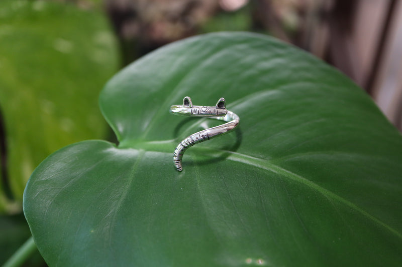 A farther view of the sterling silver cat wrap ring shown on a dark green leaf.