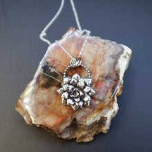 Load image into Gallery viewer, A handmade sterling silver multi layer succulent necklace show on top of a piece of light and dark brown petrified wood chunk.