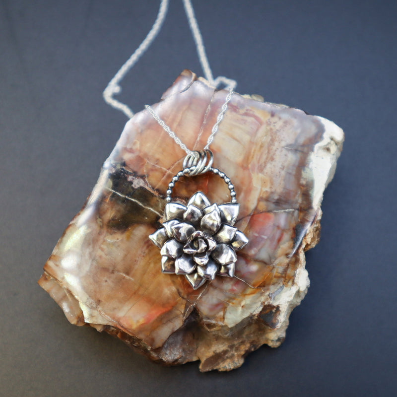 A handmade sterling silver multi layer succulent necklace show on top of a piece of light and dark brown petrified wood chunk.