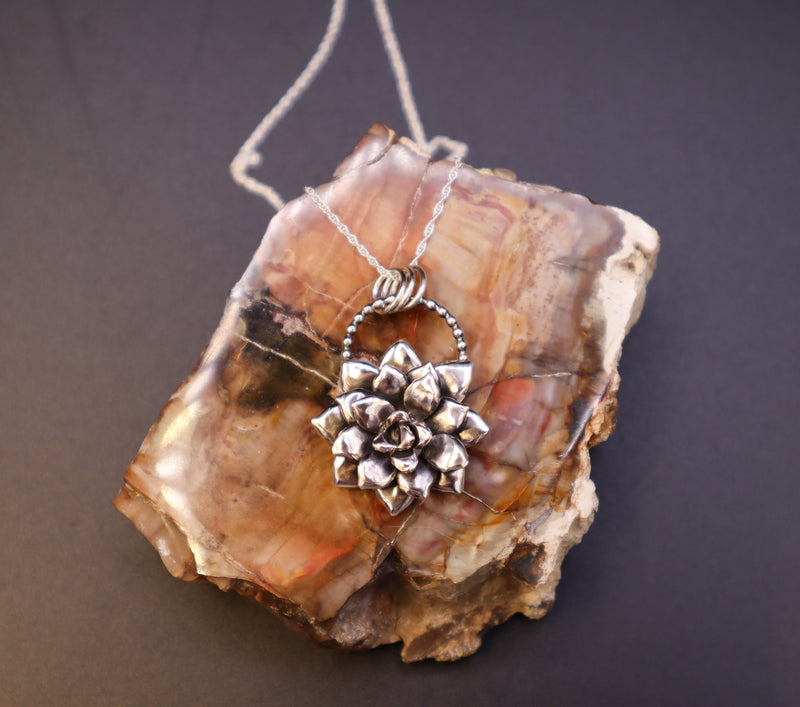 A silver handmade succulent pendant is shown on top of a light and dark brown piece of petrified wood.