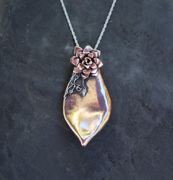 A handmade copper succulent leaf with a baby and it's rootlets at the top made out of stelring silver. The pendant is on a silver chain and shown on top of a dark grey piece of slate.