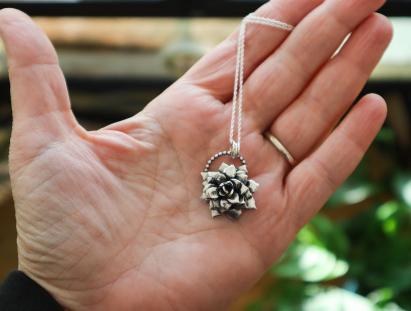 A hand holding a sterling silver succulent necklace to show size. It is about 1 inch tall and shown on a silver necklace.