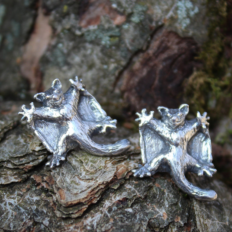 Handmade sterling silver sugar glider earrings. They are about 1/2 inch tall and shown on a piece of tree bark.