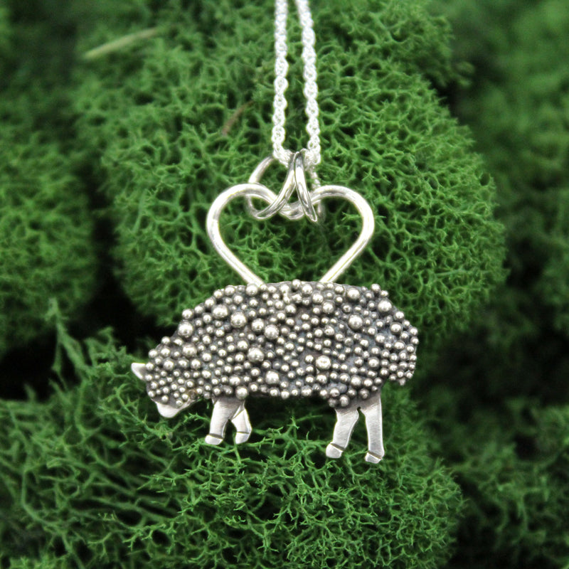 A handmade sterling silver fluffy sheep necklace. It is shown on a clump of bright green moss.