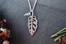 Load image into Gallery viewer, A small silver monstera leaf necklace is shown on a piece of dark grey slate.