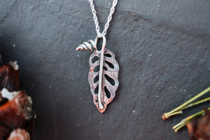 A small silver monstera leaf necklace is shown on a piece of dark grey slate.
