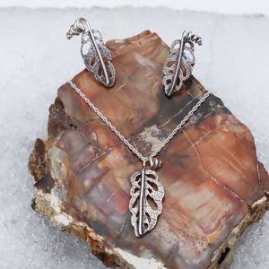 A set of sterling silver jewelry that look like small monstera adansonii leaves. A necklace, earrings, and pendant are shown on a piece of petrified stone in pretty brown colors.