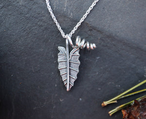 A small sterling silver alocasia polly necklace shown on a dark grey slate.