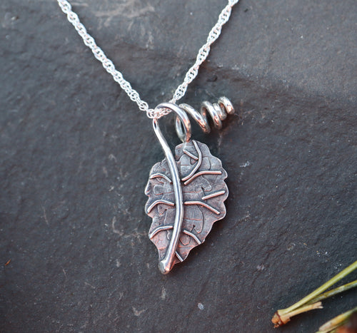 A sterling silver begonia leaf is shown on top of a dark slate tile with a silver necklace attached to it.
