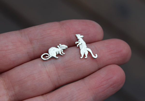 A hand is shown holding a pair of mismatched silver rat stud earrings.