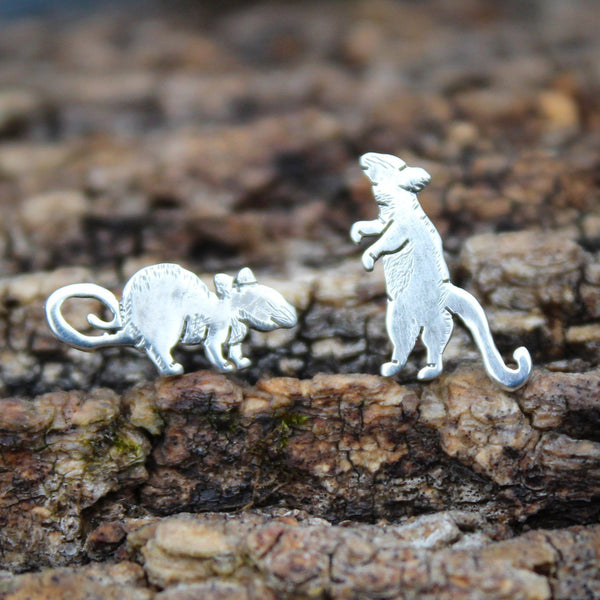 Tiny mismatched sterling silver rat earrings. One is standing up with his tiny paws tucked and the other is standing on the ground with a curled tail. They are shown on a piece of dark tree bark.