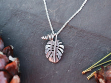 Load image into Gallery viewer, A small handmade monstera deliciosa necklace is shown on a dark grey piece of slate.