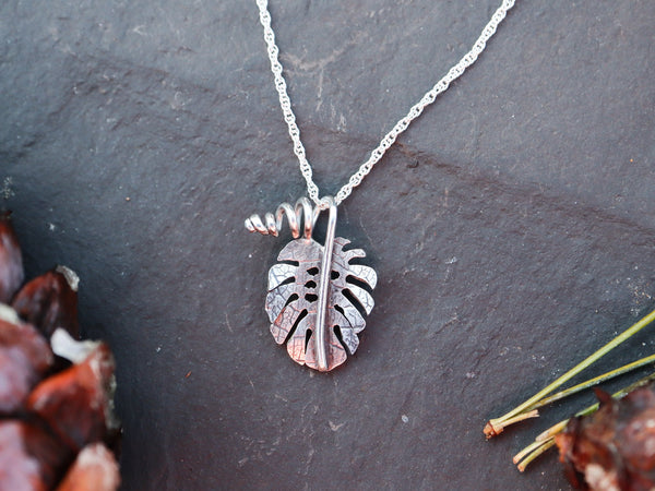 A small handmade monstera deliciosa necklace is shown on a dark grey piece of slate.