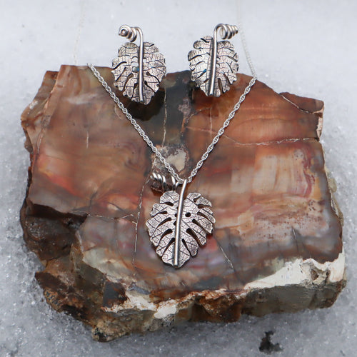 a set of jewelry featuring a monstera deliciosa necklace charm with a matching set of sterling silver monstera stud earrings. The set is shown in a piece of petrified wood.