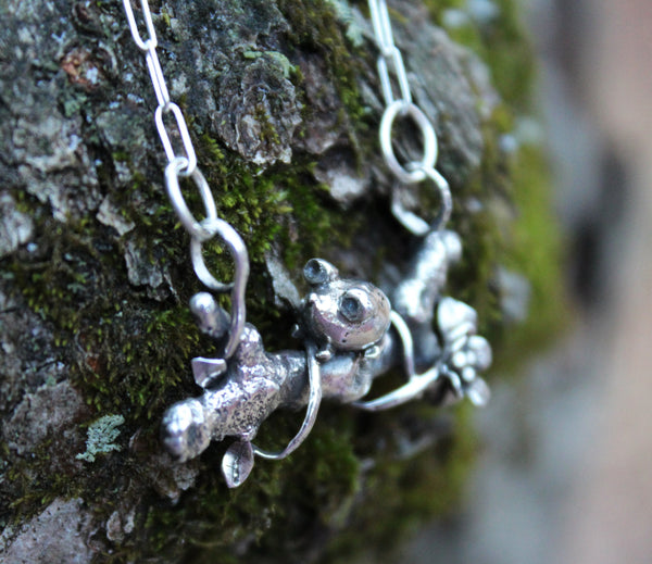 The side view of the mouse necklace on a tree branch.