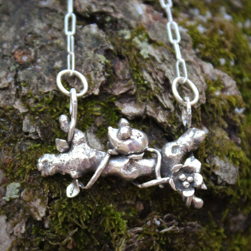 A tiny sterling silver one of a kind mouse necklace. The tiny mouse is sitting on a silver tree branch wrapped with a silver vine and a little flower at the bottom of the branch. The necklace is shown on a piece of mossy tree bark.