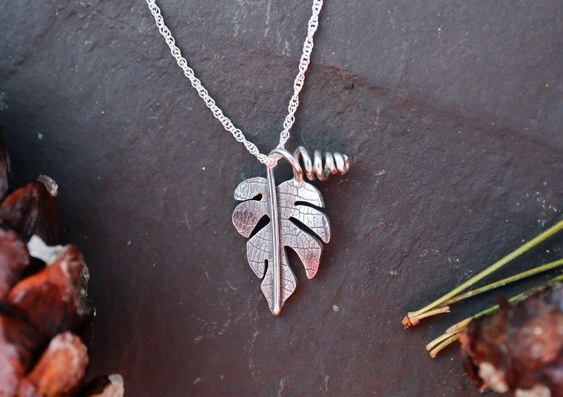 A small sterling silver rhaphidophora tetrasperma pendant with a necklace is shown in front of a dark gray slate tile.