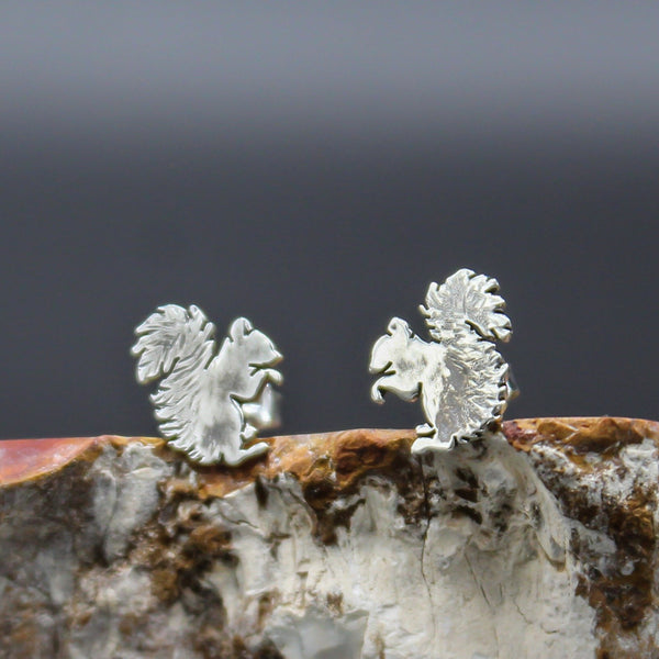 Tiny handmade silver squirrel stud earrings. They are holding their front paws to their chests and have fuzzy tails. They are shown on a piece of stone.