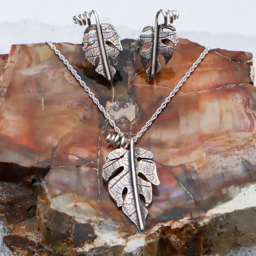 A photo of sterling silver handmade rhaphidophora tetrasperma necklace and earring set. They are shown on a piece of petrified wood with snow in the background.