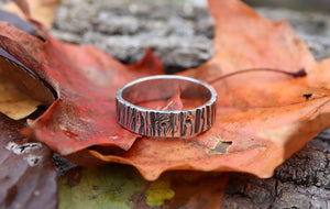 Sterling silver tree bark ring. The bark patterned ring is sitting on top of some brightly colored fall leaves. It is made by The Striped Cat Metalworks.