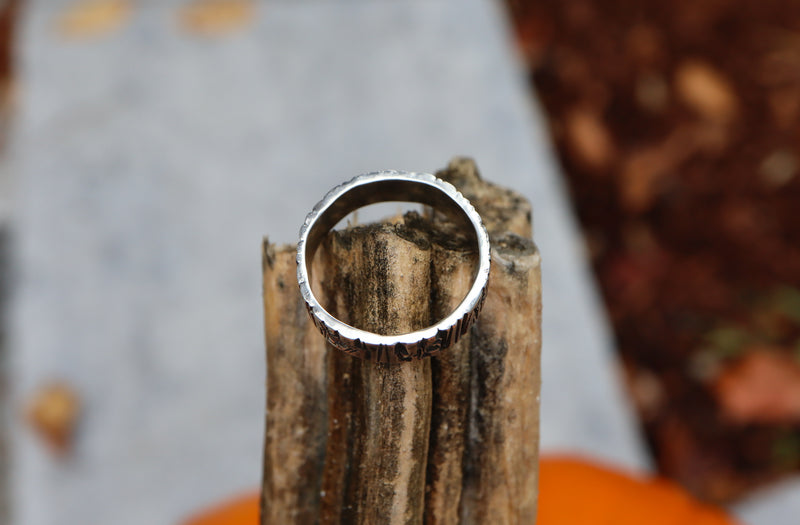 The side of a tree bark patterned silver ring shown on it's side to show how thick the silver is that the ring is made from. The ring is on top of a pumpkin stem.