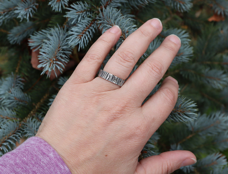 Someone wearing a sterling silver handmade tree bark ring pictured in front of an evergreen tree. The ring is made by The Striped Cat Metalworks in Massachusetts.