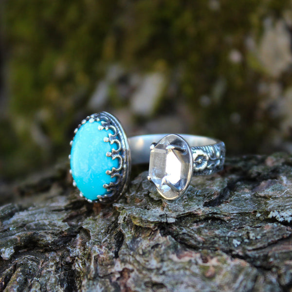 A handmade herkimer diamond and Kingman turquoise open ring. It is adjustable with a thick floral band. It is shown on a piece of tree bark.