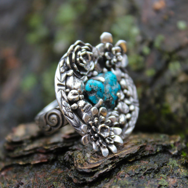 A one of a kind turquoise rough succulent garden ring. The ring face is round and features several handmade little succulent plants with tiny silver rocks between them. The turquoise stone is a rough piece and not shaped but came naturally in a heart shape at the center of the ring.