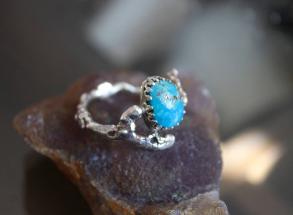 A side view of the turquoise with pyrite twig ring. It is shown on a piece of purple stone.