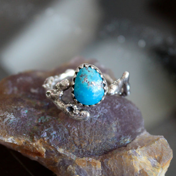 A handmade turquoise with pyrite twig ring. The silver twig band looks realistic and holds the center turquoise stone in the center of the ring.