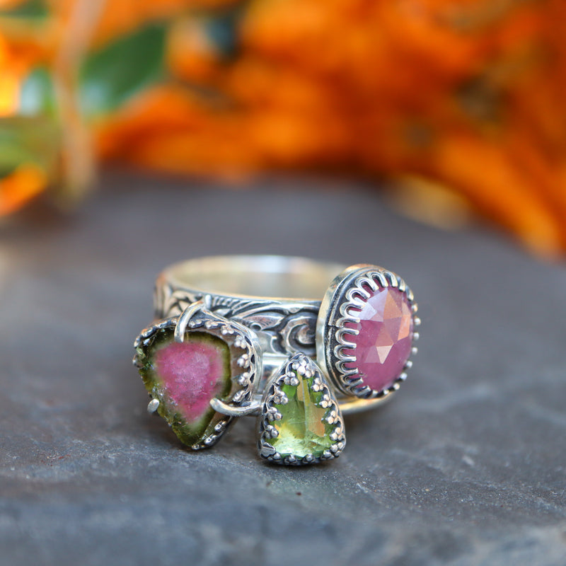 A set of three stacking rings. One ring is a pink sapphire with a rose cut stone. One ring is a triangular shaped grass green peridot stone. The third ring is a triange shaped piece of watermelon tourmaline. They are shown stacked on a piece of dark grey slate.