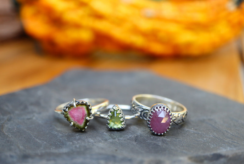 The three rings sitting next to each other instead of stacked. A watermelon tourmaline ring, a green peridot ring, and a pink sapphire ring are all shown in a dark grey piece of slate. e